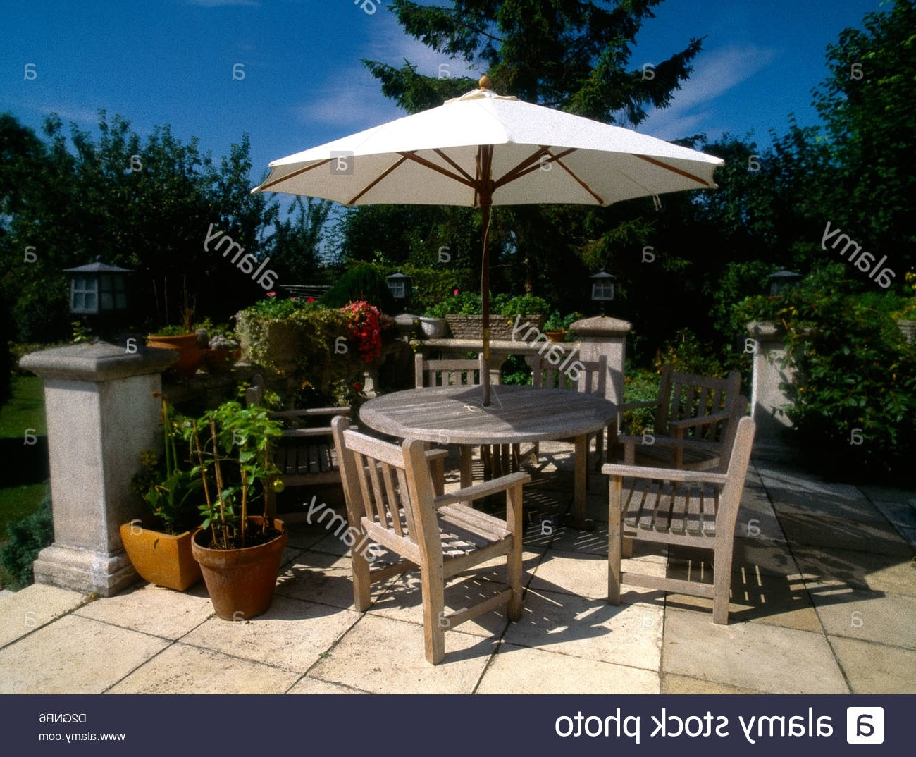 2018 Patio Table And Chairs With Umbrellas Pertaining To Wooden Garden Furniture Table & Chairs & Sun Shade Umbrella Stock (Gallery 16 of 20)