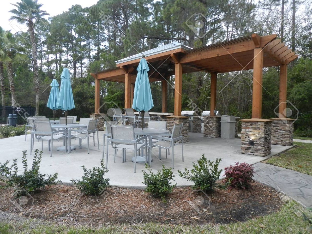 Recent Patio Furniture With Umbrellas On Stone Patio Near Upscale Condo In Upscale Patio Umbrellas (Gallery 19 of 20)