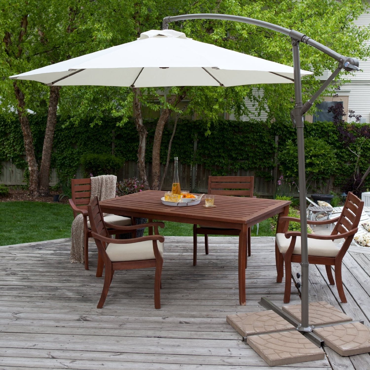 Round White Fabric Patio Umbrella With Black Base Over Dark Brown Intended For Recent Patio Umbrellas With Table (View 11 of 20)