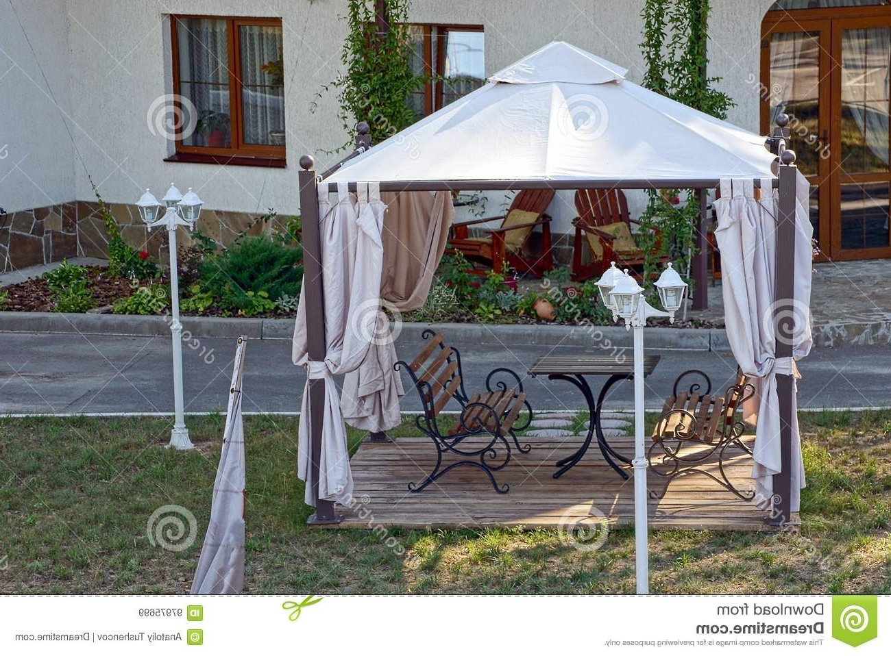 Recent Outdoor Gazebo Lanterns With Regard To Open Gazebo With Benches On The Lawn With Lanterns Near The Road (View 6 of 20)